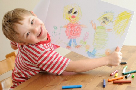 Boy proudly showing the picture he has drawn