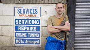 Young man in overalls next to garage sign