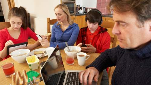Family using media and technology,eating breakfast