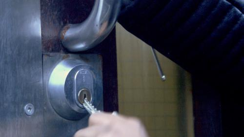 A still from the film of a key in the door
