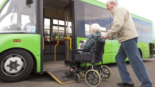 Older couple getting on bus, one in a wheelchair. The ramp of the bus is lowered.