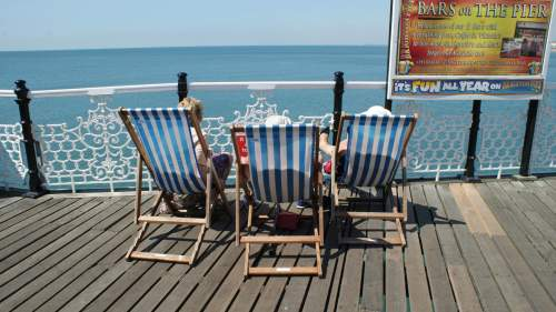 Three people relaxing in deckchairs at the seaside. Photo by Becks Hobbs Photography