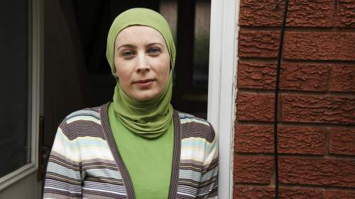 Woman in headscarf standing at the door of her house