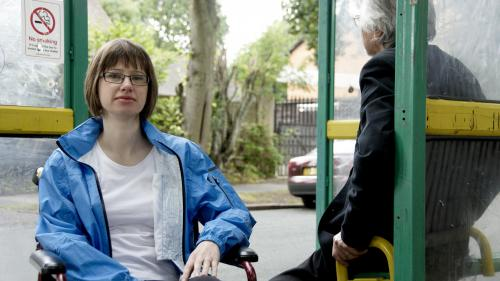 Woman in wheelchair and man sat on bench at bus stop