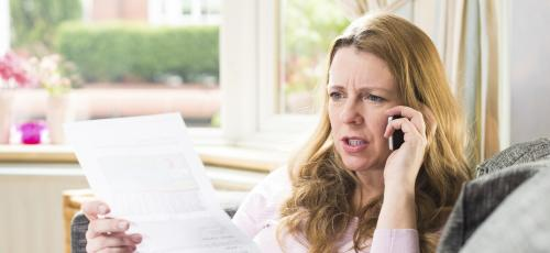Woman on phone looking at letter