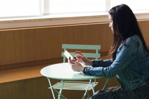 Woman sat at a table looking at her mobile phone