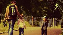 Dad with kids walking in the park. Photo by Emy Lou Photography