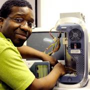 Black man mending computer